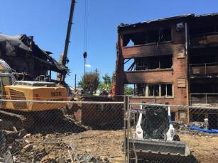 Crews with canine unit focus on a corner of the Flower Branch apartments in Silver Spring, Maryland. An explosion and fire tore through the apartment complex in the late night hours of Aug. 10. At least five people died in the blast, police said Aug. 14. (WTOP/Megan Cloherty)