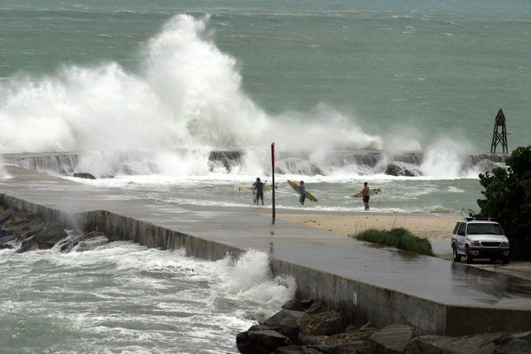 epa000268941 Surfers stand in front of the breakwater that protects the entrance to Haulover Cut, which divides Haulover Beach and Bal Harbour, in Miami, Florida, during a storm caused by Hurricane Frances on Saturday 04 September 2004. Surfers gathered in that area this morning to see the heavy sea and challenge the waves. It is expected that Frances' core center, a category 2 storm, enters through Florida's western coast Saturday night.  EPA/Ricardo Ferro