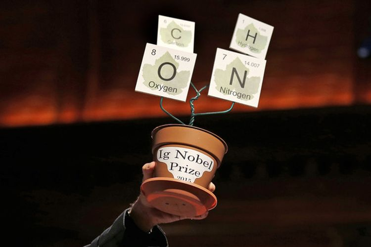The Ig Nobel trophy, made from an empty flower pot and letters from the element charts, is hoisted up during a performance at the Ig Nobel Prize ceremony at Harvard University, in Cambridge, Mass., Thursday, Sept. 17, 2015. The Ig Nobel prize is an award handed out by the Annals of Improbable Research magazine at Harvard University for silly sounding scientific discoveries that often have surprisingly practical applications. (AP Photo/Charles Krupa)