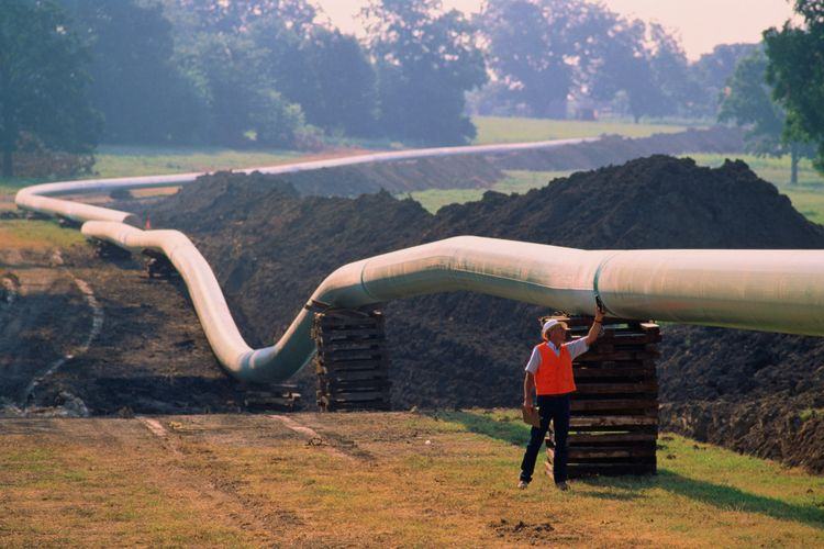 Worker checking welds on natural gas pipeline running through field