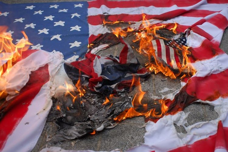 A small group of 'Muslims Against the Crusades' commemorated the attacks 9 years ago today on the World Trade Center in New York by burning a flag in front of the US Embassy with a heavy police presence monitoring. London, United Kingdom 11/09/2010.