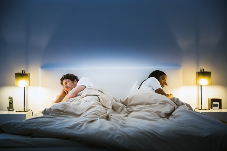 Couple ignoring each other on bed